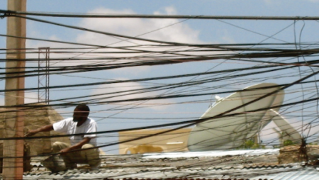 A photo of a man sitting with electricity wires, taken by Dr Stremlau during her fieldwork